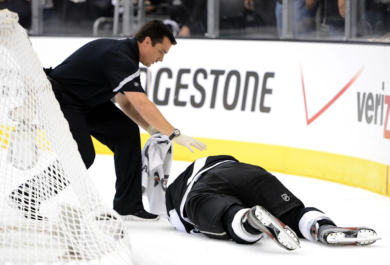 LOS ANGELES, CA - JUNE 11:  Rob Scuderi #7 of the Los Angeles Kings lays on the ice after being boarded by Steve Bernier #18 of the New Jersey Devils (not in photo) in Game Six of the 2012 Stanley Cup Final at Staples Center on June 11, 2012 in Los Angeles, California.  (Photo by Harry How/Getty Images)