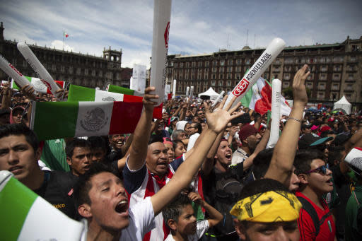 Fan's celebrate Mexico's win during the Mexico vs. Germany World Cup soccer match, as they watched it on an outdoor screen in Mexico City's Zocalo, Sunday, June 17, 2018. Mexico won it's first match against Germany 1-0. (AP Photo/Anthony Vazquez)