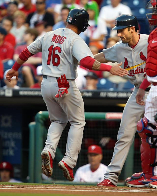 St Louis Cardinals Matt Carpenter, right, cheers on Kolten Wong after they both scored on a double by Matt Holliday in the first inning of a baseball game against the Philadelphia Phillies, Friday, Aug. 22, 2014, in Philadelphia. (AP Photo/Laurence Kesterson)
