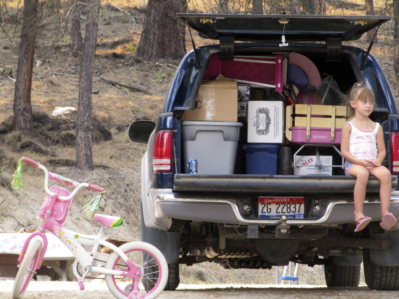 Lizzie Morris, 4, waits for her grandmother, Lorie Winmill, to load their belongings into a vehicle as they prepare to evacuate from their home in Featherville, Idaho on Wednesday, Aug. 15, 2012. They were among residents warned that they will likely have to evacuate their homes because of a nearby wildfire that has burned 100 square miles.  (AP Photo/Jessie L. Bonner)