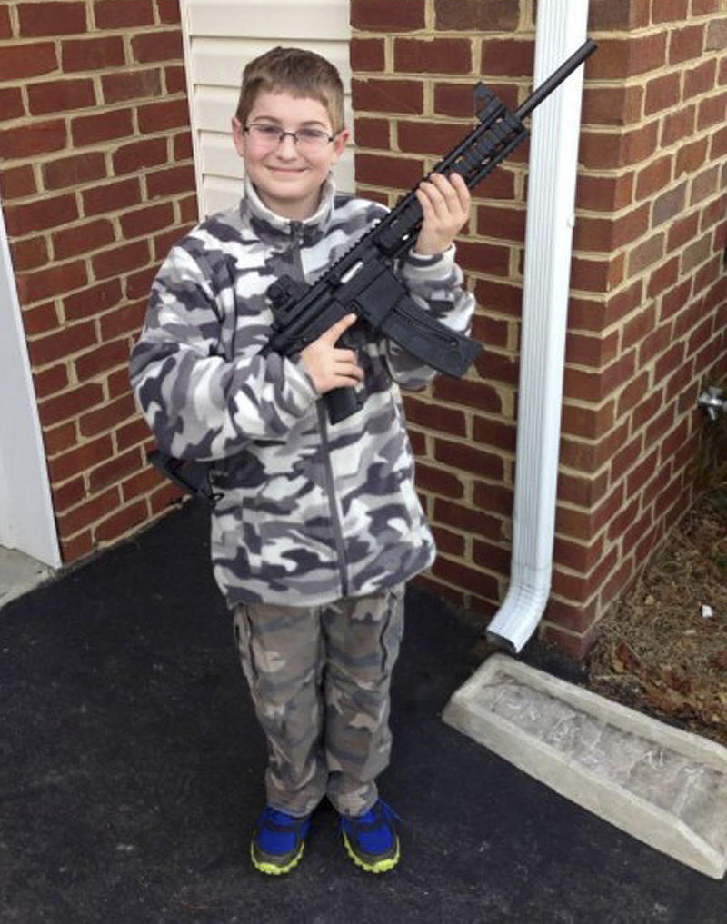 "FILE - This undated file photo provided by Shawn Moore shows his son Josh, 10, holding a rifle his father gave him for his 11th birthday, at their home in Carneys Point, N.J.  The Moore family claims this photo, posted on Facebook, led the state's child welfare agency to the family's house, Friday, March 15, 2013, demanding to be let inside to inspect their guns. In a letter released Wednesday, March 27, 2013, New Jersey Gov. Chris Christie wrote Attorney General Jeffrey Chiesa, saying the inquiry raises ""troubling questions,"" and asked the attorney general to investigate the state's visit to the Moore's home. (AP Photo/Shawn Moore, FILE)"