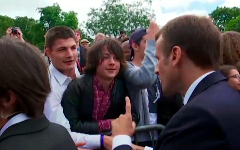 French President Emmanuel Macron speaks with the teenage boy in Paris - TF1