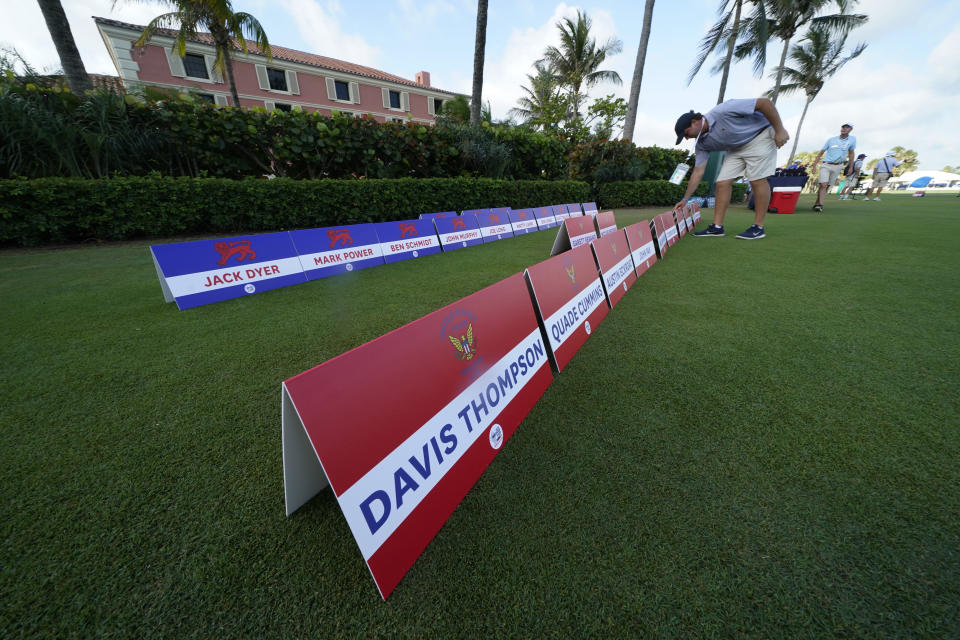 A man places signs with team members names for the USA team and the Great Britain and Ireland team, on a practice day for the Walker Cup golf tournament, which starts tomorrow, at Seminole Golf Club in Juno Beach, Fla., Friday, May 7, 2021. (AP Photo/Gerald Herbert)