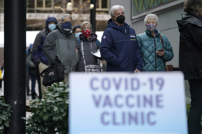 FILE - In this an. 24, 2021, file photo, people stand near a sign as they wait in line to receive the first of two doses of the Pfizer vaccine for COVID-19 at a one-day vaccination clinic set up in an Amazon.com facility in Seattle and operated by Virginia Mason Franciscan Health. Scientists say it's still too early to predict the future of the coronavirus, but many doubt it will ever go away entirely. (AP Photo/Ted S. Warren, File)
