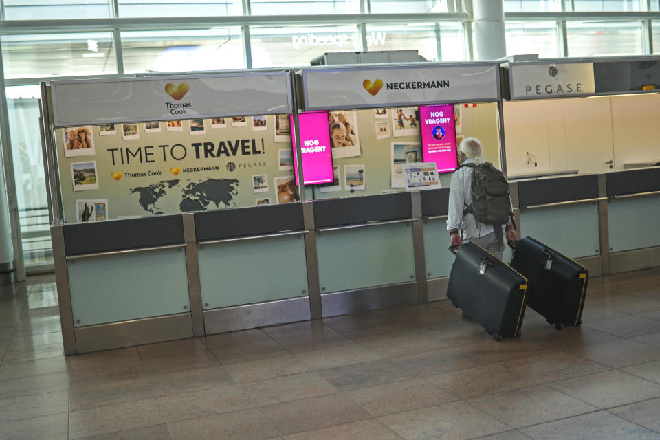 A traveller stands by an empty service counter of Neckermann, part of Thomas Cook tour company, at the Brussels international airport in Brussels, Monday, Sept. 23, 2019. British tour company Thomas Cook collapsed early Monday after failing to secure emergency funding, leaving tens of thousands of vacationers stranded abroad. (AP Photo/Francisco Seco)