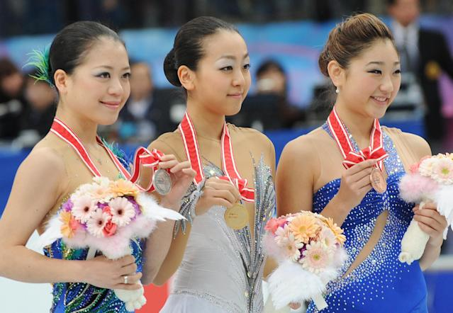 Accompanied by second place Akiko Suzuki (C) of Japan and third placed Mirai Nagasu (R) of the US, Mao Asada (C) of Japan poses for photographers during the awarding ceremony for the women's event in the NHK Trophy, the last leg of the six-stage ISU figure skating Grand Prix series, in Rifu, northern Japan, on November 24, 2012. AFP PHOTO/Toru YAMANAKATORU YAMANAKA/AFP/Getty Images