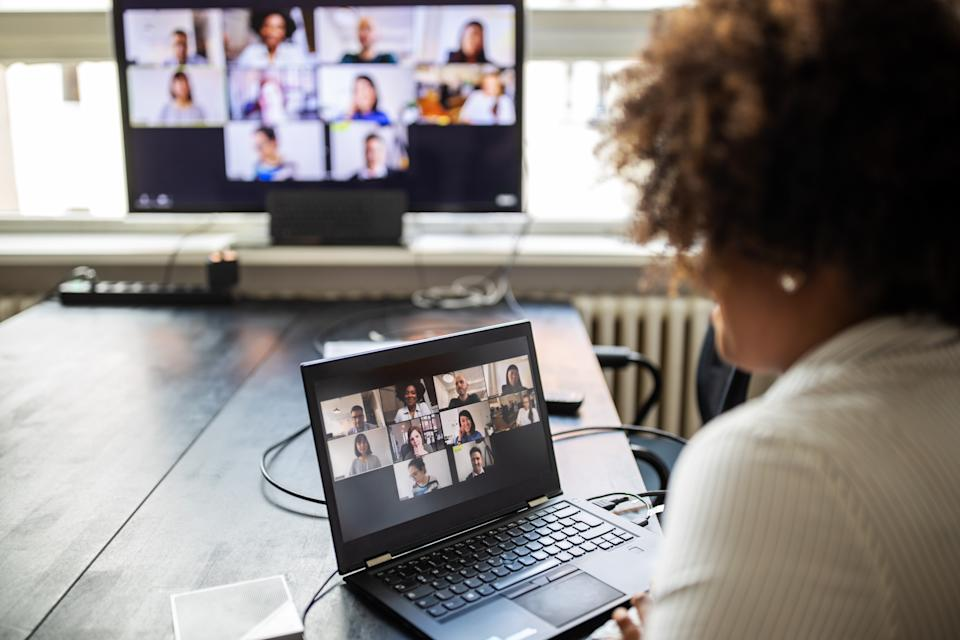 Businessman sitting in conference room and having a video call meeting. Woman on a video conference meeting at office.