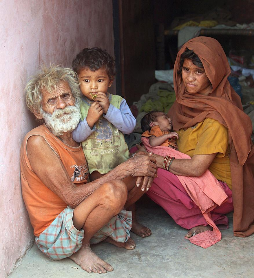 Ramajit Raghav, 96, sits with his two-year-old-son Vikramjit, wife Shankuntala and new arrival Ranjit (Rex)