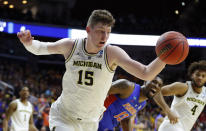 <p>Michigan center Jon Teske (15) runs down a rebound ahead of Florida center Kevarrius Hayes (13) during a second round men's college basketball game in the NCAA Tournament, Saturday, March 23, 2019, in Des Moines, Iowa. (AP Photo/Charlie Neibergall) </p>