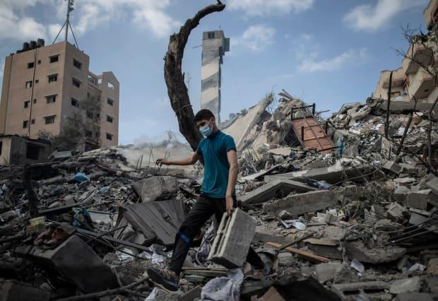 A Palestinian man inspects the damage of a six-storey building destroyed by an early-morning Israeli airstrike in Gaza City Tuesday.