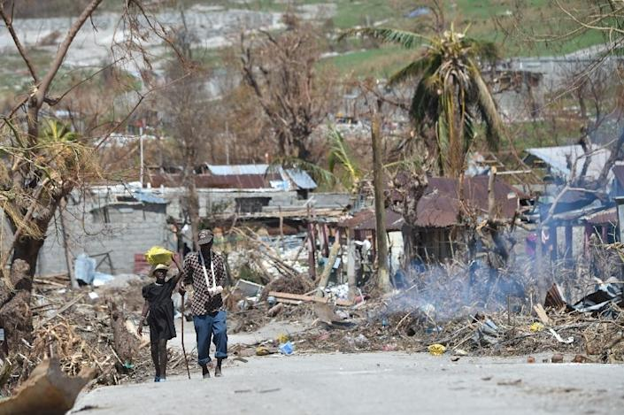 People walk down a debris covered street in the commune of Port-a-Piment, in Les Cayes, in southwest Haiti, on October 11, 2016 (AFP Photo/Hector Retamal)