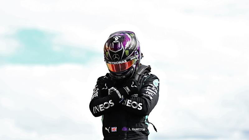 Lewis Hamilton poses with 'Wakanda Forever' on top of his Mercedes.