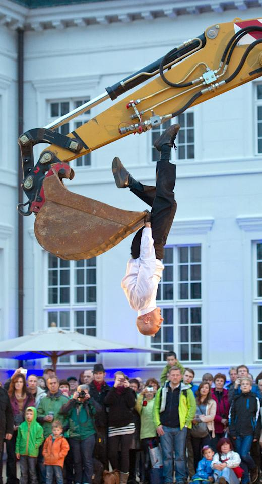 French dancer Philippe Priasso performs a Pas de Deux with a Digger during the Neuhardenberg-Nacht (Neuhardenberg Night) on May 18, 2013 at Neuhardenberg Palace in Neuhardenberg, eastern Germany. Performances, music and fireworks were on the programme of the cultural festival organised by the Neuhardenberg Palace Foundation.      AFP PHOTO / PATRICK PLEUL