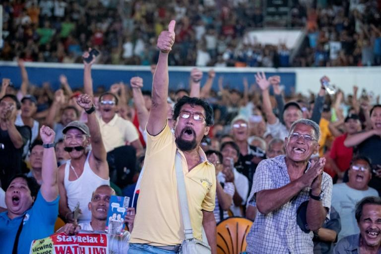 Filipino fans watch Manny Pacquiao fight against Keith Thurman beamed from the US at a covered basketball court in Manila