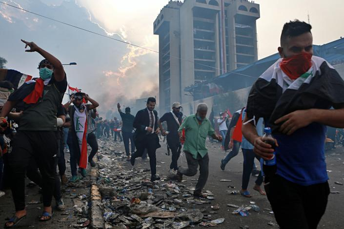 Anti-government protesters run to take cover while Iraqi Security forces fire tear gas during a demonstration in Tahrir Square in Baghdad, Iraq, Monday, Oct. 28, 2019. (Photo: Khalid Mohammed/AP)