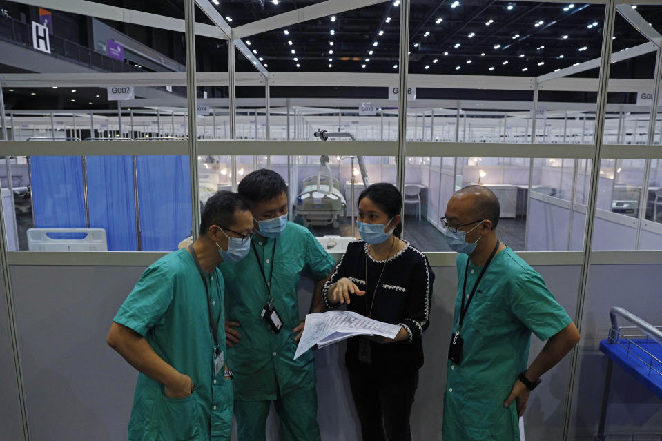 Medical workers make preparations at a temporary field hospital set up at Asia World Expo in Hong Kong, Saturday, Aug. 1, 2020. The new COVID-19 patient holding facility can accommodate up to 500 adult patients in stable conditions. The facility which is located near the Hong Kong International Airport is a big convention and exhibition facility and was previously used as a coronavirus testing center for incoming travelers. It's transformed into a treatment facility so that it helps freeing up hospital beds for the serious patients. (AP Photo/Kin Cheung)