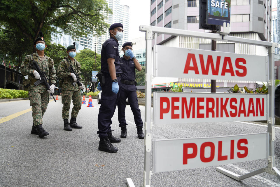 Police and army officers check vehicles at a roadblock to ensure that people abide by a movement control order in downtown Kuala Lumpur, Malaysia, Wednesday, Oct. 14, 2020. Malaysia will restrict movements in its biggest city Kuala Lumpur, neighboring Selangor state and the administrative capital of Putrajaya from Wednesday to curb a sharp rise in coronavirus cases. (AP Photo/Vincent Thian)
