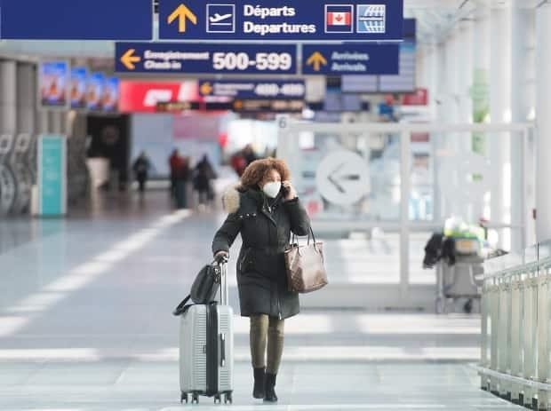 An air passenger wears a face mask while walking through Montreal–Trudeau International Airport in December 2020. People are already booking vacations to overseas locations, but one epidemiologist says global travel won't be back to normal until at least 2024.  (Graham Hughes/CP - image credit)