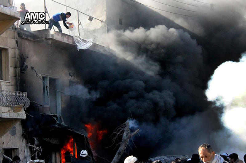 In this citizen journalism image provided by Aleppo Media Center (AMC), an anti-Bashar Assad activist group, and authenticated based on its contents and other AP reporting, a Syrian man, top left, tried to extinguish a fire with a bucket of water at shops following a Syrian government forces warplane attack, at al-Bab neighborhood in Aleppo, Syria, Saturday, Feb. 1, 2014. Syrian military helicopters dropped barrels packed with explosives on rebel-held areas of the northern city of Aleppo on Saturday, killing at least a dozen of people including a family trapped in a car, as government forces inched closer to opposition-held areas. (AP Photo/Aleppo Media Center, AMC)