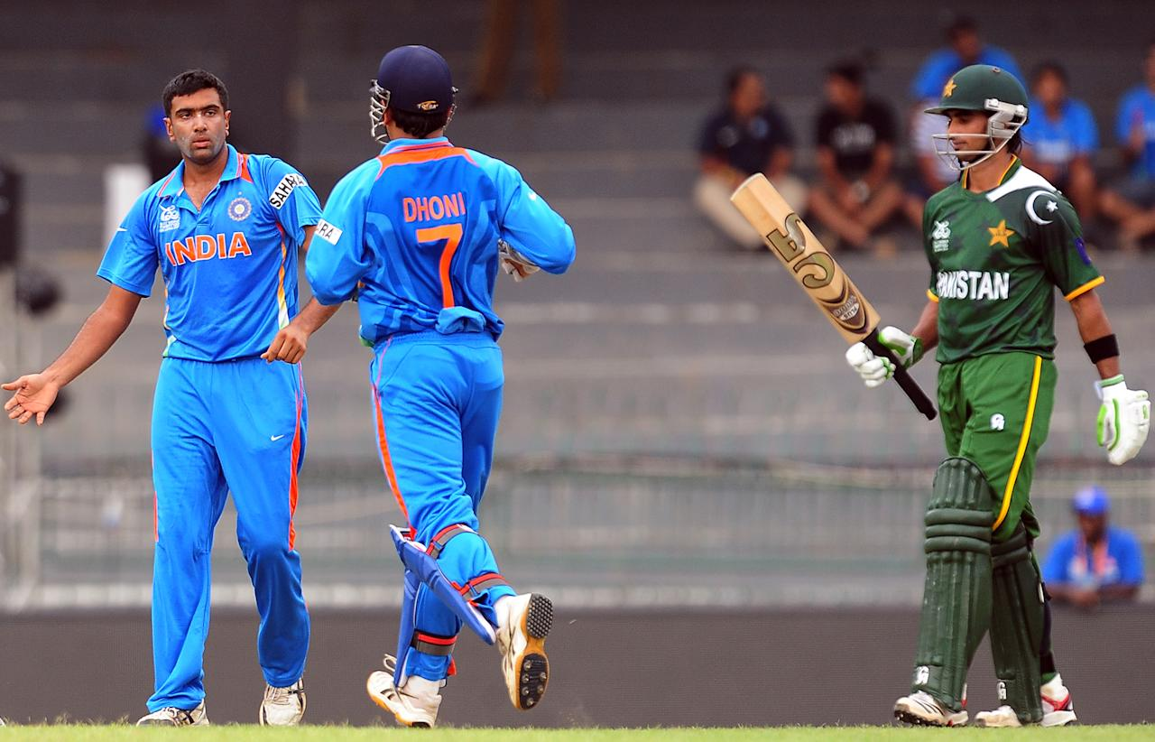 Indian cricketer Ravichandran Ashwin (L) celebrates with his wicketkeeper Mahendra Singh Dhoni (C) after he dismissed Pakistan's Imran Nazir (R) during a World Twenty20 warm-up match between India and Pakistan at The R. Premadasa Cricket Stadium in Colombo on September 17, 2012. AFP PHOTO/ LAKRUWAN WANNIARACHCHI