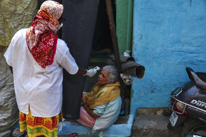 An Indian health worker checks body temperature of a woman during a door-to-door survey being conducted as a precaution against COVID-19 in Hyderabad, India, Thursday, May 6, 2021. (AP Photo/Mahesh Kumar A.)