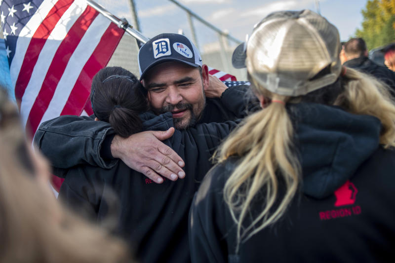 Saginaw resident Michael Perez and other members celebrate during the 40th and final day of the United Auto Workers strike against General Motors outside of the Flint Assembly Plant, Friday, Oct. 25, 2019, in Flint, Mich. Striking General Motors factory workers are putting down their picket signs after approving a new contract that will end a 40-day strike that paralyzed the company's U.S. production. (Jake May/MLive.com/The Flint Journal via AP)