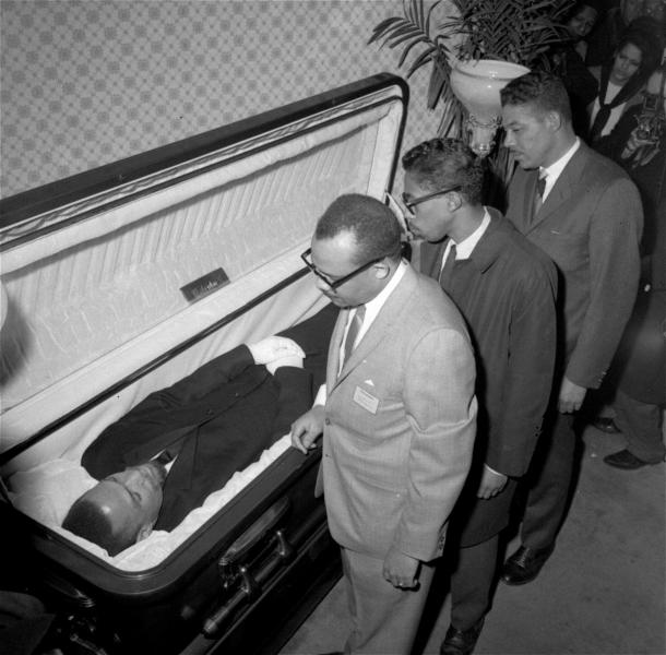"File - In this Feb. 24, 1965, file photo, the body of Malcolm X, black nationalist leader who was slain February 21, 1965, at a rally of his organization, is viewed by newsmen at the Unity Funeral Home, Eighth Avenue and 126th Street in New York City. ""Who Killed Malcolm X?"" currently streaming on Netflix dives into questions surrounding his assassination and allegations of a botched investigation. (AP Photo/File)"