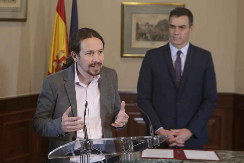 Podemos party leader Pablo Iglesias speaks as Spain's caretaker Prime Minister Pedro Sanchez looks on after signing an agreement at the parliament in Madrid, Spain, Tuesday, Nov. 12, 2019. The leaders of Spain's Socialist party and the left-wing United We Can (Podemos) party say they have reached a preliminary agreement toward forming a coalition government. But the deal announced Tuesday won't provide enough votes in parliament for the Socialists, who won a general election, to take office without the support of other parties. (AP Photo/Paul White)