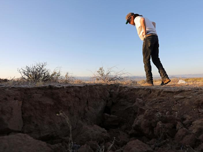 A man on July 4, 2019, looking into a fissure that opened in the desert during a powerful earthquake that struck near Ridgecrest.