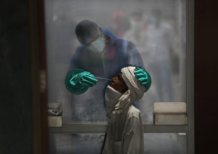 FILE - In this Monday, July 6, 2020, file photo, a health worker takes a nasal swab of a person for a COVID-19 test at a hospital in New Delhi, India. In just three weeks, India's confirmed cases shot up from the world's sixth to the third-worst hit country by the coronavirus pandemic, according to a tally by Johns Hopkins University. India's fragile health system was bolstered during stringent monthslong lockdown but could still be overwhelmed by an exponential rise in infections. (AP Photo/Manish Swarup, File)
