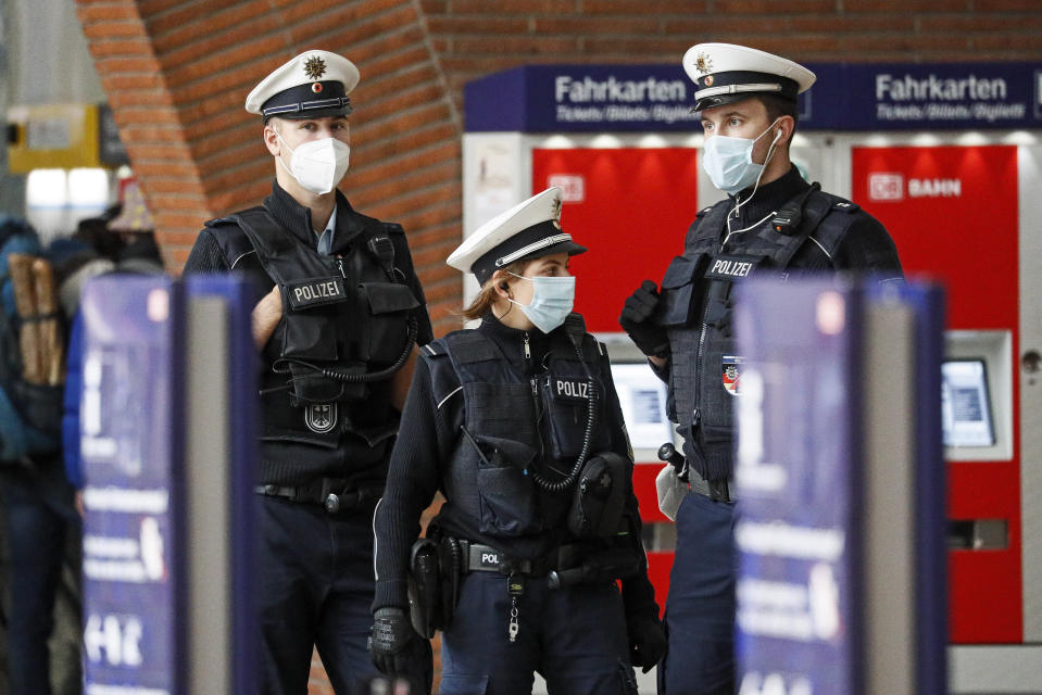 Police with face masks control the coronavirus orders at the train station in Cologne, Germany, Thursday, Oct. 15, 2020. The city exceeded the important warning level of 50 new infections per 100,000 inhabitants in seven days. More and more German cities become official high risk corona hotspots with travel restrictions within Germany. (AP Photo/Martin Meissner)