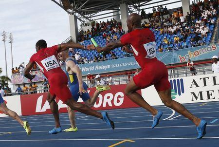 FILE PHOTO - Trell Kimmons (R) of the U.S. fails to pass the baton to his teammate Rakieem Salaam (L) within the allowed space on the track, during a qualifying heat of the men's 4x100 metres relay event during the IAAF World Relays Championships in Nassau, Bahamas, May 25, 2014. REUTERS/Mike Segar