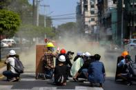 Protesters take cover as riot police officers fire teargas canister during a rally against the military coup in Yangon
