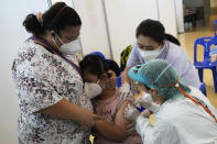 A mother comforts her child receiving the Pfizer-BioNTech COVID-19 vaccine at a hospital in Bangkok, Thailand, Tuesday, Sept. 21, 2021. Bangkok Metropolitan Administration inoculated 12-18 year old students Tuesday as part of its attempt to reopen on-site schools. (AP Photo/Sakchai Lalit)