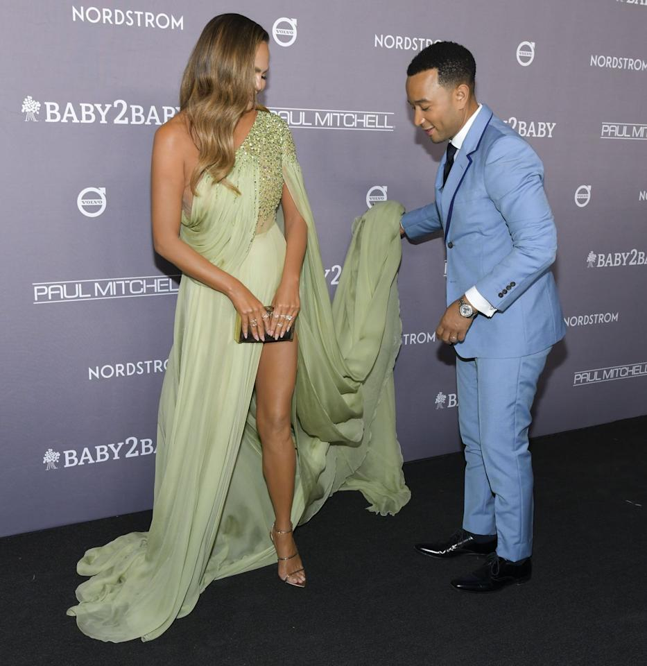 <p>The couple attended the Baby2Baby gala in California on Saturday night, and Legend made sure the train on his wife's green dress was positioned just right for that photo finish.</p>