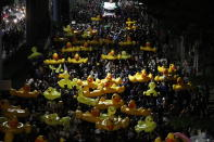 Protesters carry inflatable yellow ducks, which have become good-humored symbols of resistance during anti-government rallies, while marching towards the base of the 11th Infantry Regiment, a palace security unit under direct command of the Thai king, Sunday, Nov. 29, 2020 in Bangkok, Thailand. Pro-democracy demonstrators are continuing their protests calling for the government to step down and reforms to the constitution and the monarchy, despite legal charges being filed against them and the possibility of violence from their opponents or a military crackdown. (AP Photo/Sakchai Lalit)