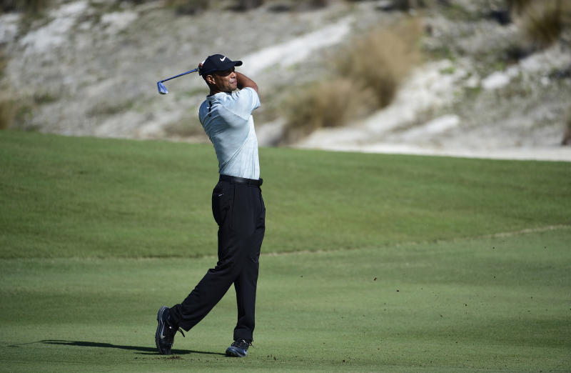 Tiger Woods hits from the fairway at the third hole during the first round of the Hero World Challenge at the Albany Golf Club in Nassau, Bahamas, Thursday, Nov. 29, 2018. Woods now is No. 13 in the world as he hosts this holiday tournament for the 20th time. (AP Photo/Dante Carrer)
