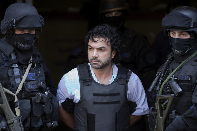 "Policemen escort alleged Colombian drug lord Henry de Jesus Lopez, also known as ""Mi Sangre,"" or ""My Blood,"" in Buenos Aires, Argentina,  Wednesday, Oct. 31, 2012. Lopez, a former paramilitary wanted in Colombia and the U.S. on charges of organized crime, drug trafficking and terrorism, was arrested in suburban Buenos Aires, Tuesday, Oct. 30, 2012. (AP Photo/Victor R. Caivano)"