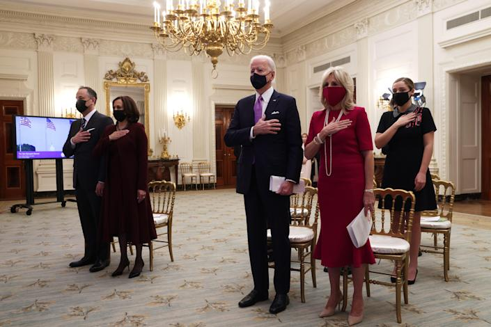 President Joe Biden, first lady Jill Biden, Vice President Kamala Harris and second gentleman Doug Emhoff listen to the national anthem as they watch the virtual presidential inaugural prayer service in the State Dining Room of the White House Jan. 21, 2021.