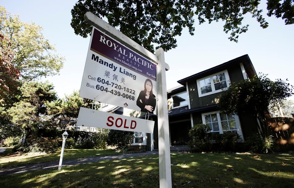 A real estate for sale sign is pictured in front of a home in Vancouver, British Columbia, Canada. REUTERS/Ben Nelms