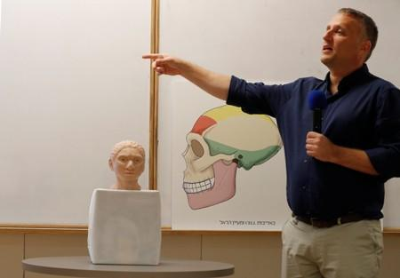 Hebrew University professor Liran Carmel, gestures next to the artistic rendering of the head and face of a 13-year-old girl from the the prehistoric human species, Denisovan, based on technology developed by Carmel and his team, in Jerusalem