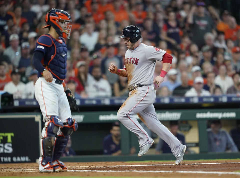 Boston Red Sox's Steve Pearce, right, scores as Houston Astros catcher Robinson Chirinos looks on during the third inning of a baseball game Sunday, May 26, 2019, in Houston. (AP Photo/David J. Phillip)