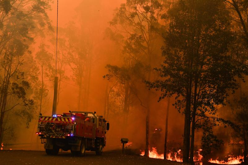Fire trucks approaching a bushfire in Werombi, 50km southwest of Sydney, on Friday.
