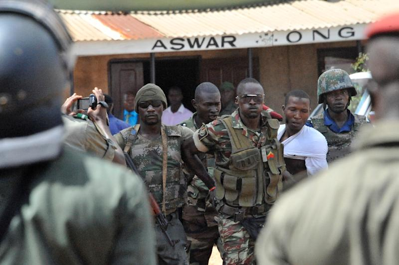 Security forces re-detain a prisoner after a mutiny broke out in the civil prison of Conakry on November 9, 2014 in Guinea