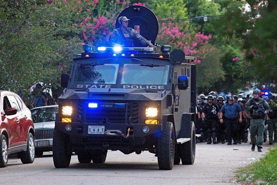 An armored police truck leads a troop of police through a residential neighborhood in Baton Rouge, La. on Sunday, July 10, 2016. After an organized protest in downtown Baton Rouge protesters wondered into residential neighborhoods and toward a major highway that caused the police to respond by arresting protesters that refused to disperse. (AP Photo/Max Becherer)
