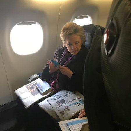 Hillary Clinton looks at a newspaper carrying an article about Vice President Mike Pence's use of personal email