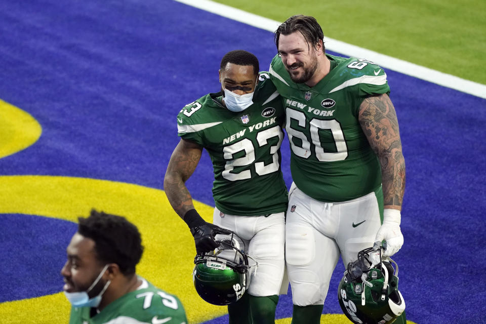 New York Jets cornerback Arthur Maulet (23) hugs center Connor McGovern (60) after a win over the Los Angeles Rams during an NFL football game Sunday, Dec. 20, 2020, in Inglewood, Calif. (AP Photo/Ashley Landis)
