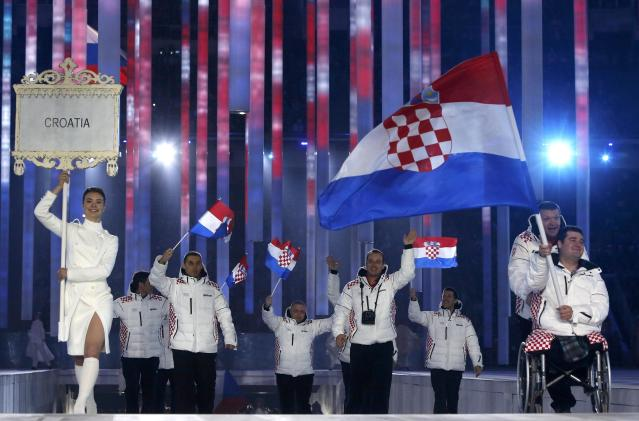 Croatia's flag-bearer Dino Sokolovic (R), leads his country's contingent during the opening ceremony of the 2014 Paralympic Winter Games in Sochi, March 7, 2014. REUTERS/Alexander Demianchuk (RUSSIA - Tags: OLYMPICS SPORT)