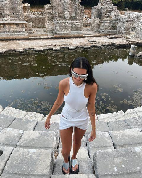 """<p>For a visit to the ruins in Butrint, Lipa stepped into a white The Attico mini dress, a pair of futuristic <a href=""""https://www.farfetch.com/uk/shopping/women/balenciaga-eyewear-swift-round-frame-sunglasses-item-16795164.aspx"""" rel=""""nofollow noopener"""" target=""""_blank"""" data-ylk=""""slk:Balenciaga sunglasses"""" class=""""link rapid-noclick-resp"""">Balenciaga sunglasses</a> and <a href=""""https://www.matchesfashion.com/products/1442113"""" rel=""""nofollow noopener"""" target=""""_blank"""" data-ylk=""""slk:Prada earrings"""" class=""""link rapid-noclick-resp"""">Prada earrings</a>. </p><p><a class=""""link rapid-noclick-resp"""" href=""""https://www.flannels.com/the-attico-attico-attico-mini-ld14-648239"""" rel=""""nofollow noopener"""" target=""""_blank"""" data-ylk=""""slk:SHOP DUA'S DRESS NOW"""">SHOP DUA'S DRESS NOW</a></p><p><a href=""""https://www.instagram.com/p/CSHkfH6MAJr/"""" rel=""""nofollow noopener"""" target=""""_blank"""" data-ylk=""""slk:See the original post on Instagram"""" class=""""link rapid-noclick-resp"""">See the original post on Instagram</a></p>"""