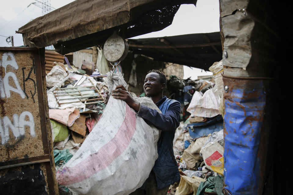 Peter Kihika, 16, who wants to become a teacher, weighs scavenged materials to be sold for recycling, at Kenya's largest landfill Dandora where Peter now works after his mother lost her job and his school was closed due to the coronavirus pandemic, in Nairobi, Kenya Saturday, Sept. 26, 2020. The United Nations says the COVID-19 pandemic risks significantly reducing gains made in the fight against child labor, putting millions of children at risk of being forced into exploitative and hazardous jobs, and school closures could exacerbate the problem. (AP Photo/Brian Inganga)